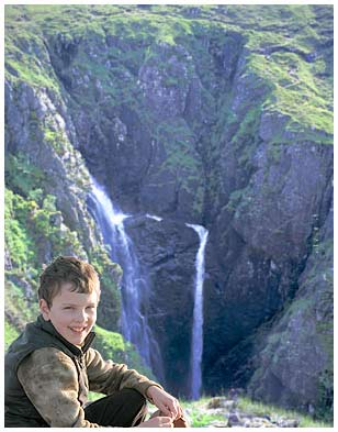 A young boy visiting the Falls of Glomach