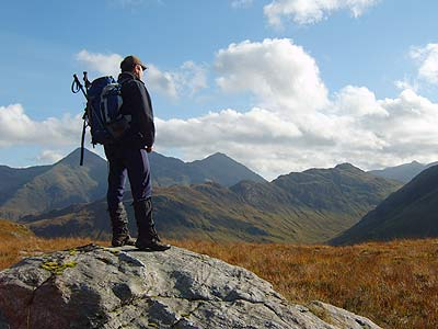 Trekking in Lochalsh - a walker on the summit of a mountain in Lochalsh
